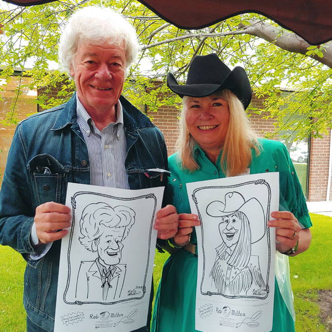 Two happy Stampede party guests with their caricatures.
