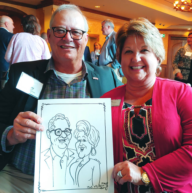 Smiling couple showing off their caricature.