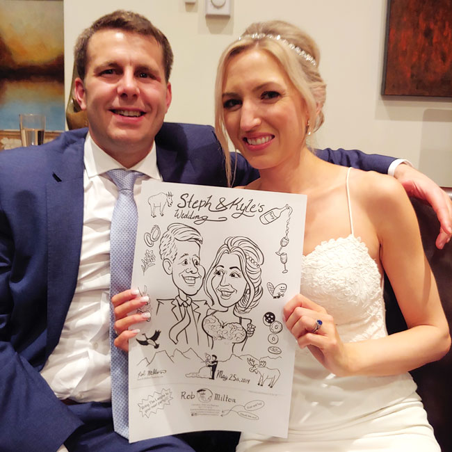Happy Bride and Groom with their caricature.